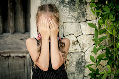 Portrait of sad little girl standing near stone wall in the day Stock Images