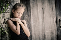 Portrait of sad little girl standing near stone wall in the day Stock Photo