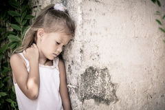Portrait of sad little girl standing near stone wall in the day Royalty Free Stock Image