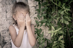 Portrait of sad little girl standing near stone wall in the day Royalty Free Stock Images