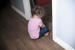 Portrait of sad little girl standing near wall in Stock Photography