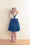 Portrait of sad little girl standing near wall Stock Image