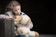 Portrait of sad little girl. Portrait of young sad little girl sitting with suitcase outdoors at the day time. Concept of sorrow Royalty Free Stock Photo