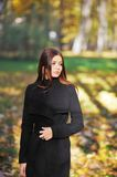 Portrait of a sad, long-haired girl in an elegant black cardigan on sunny day in autumn park. Portrait of a sad, long-haired girl in an elegant black cardigan Stock Photo