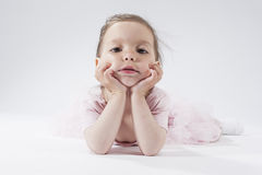 Portrait of Sad Looking Little Caucasian Blond Child Posing in Pink Dress Against White Background Stock Photography