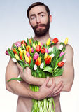 Portrait of sad man with flowers. Studio photo of a man with bouquet of tulips Royalty Free Stock Photo