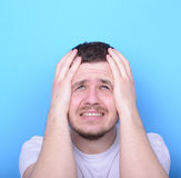 Portrait of sad man looking up against blue background Stock Photos