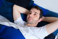 Young man lying in the bed feeling bad and trying to sleep in th. Portrait of sad man lying in the bed and trying to sleep in the morning Stock Photos