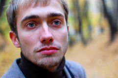 Portrait of a sad man in the park. In autumn Royalty Free Stock Photos