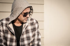 Portrait of a sad man in sunglasses sitting near the house Stock Image