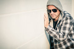 Portrait of a sad man in sunglasses sitting near the house Stock Images