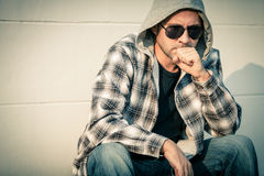 Portrait of a sad man in sunglasses sitting near the house Stock Photos