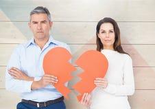 Portrait of sad mature couple holding broken hearts Royalty Free Stock Photography