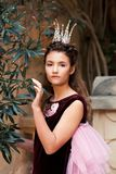 Portrait of a sad melancholy girl princess in a crown of beads and a velvet fairy dress royalty free stock images