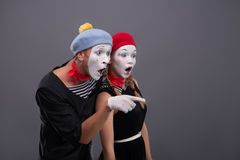 Portrait of sad mime couple crying  on. Waist-up side-view portrait of young mime couple wondering looking aside and showing with a finger at something  on grey Royalty Free Stock Photo