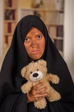 Portrait of a sad muslim girl wearing a hijab and holding her arms her teddy bear, in a blurred background Royalty Free Stock Images
