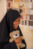 Portrait of a sad muslim girl wearing a hijab and holding her arms her teddy bear, in a blurred background Stock Image