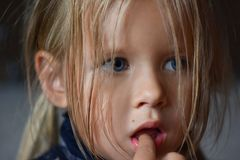 Portrait of a sad romantic little girl with big blue eyes and a finger in her mouth from Eastern Europe, close-up, dark background royalty free stock photo