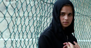 Portrait of sad schoolgirl in hooded leaning against fence