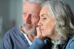 Close up portrait of sad senior couple posing at home stock images