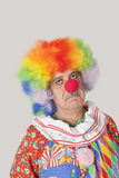 Portrait of sad senior male clown against colored background Royalty Free Stock Photography