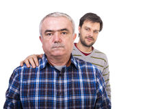 Portrait of sad senior man being comforted by his son Royalty Free Stock Photo