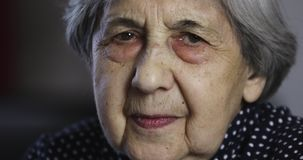 Portrait of a sad senior woman with deep wrinkles. Cute grandmother is looking at the camera stock video footage