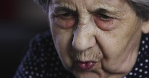 Portrait of a sad senior woman with deep wrinkles. The face of an old female model sitting at home stock video