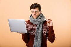 Portrait a sad sick man dressed in sweater. And scarf isolated over beige background, browsing, holding laptop computer, showing thermometer royalty free stock photo