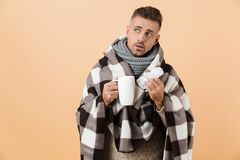 Portrait of a sad sick man wrapped in a blanket royalty free stock image