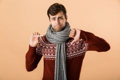 Portrait of a sad sick young man dressed in sweater. And scarf isolated over beige background, showing thermometer, showing thumbs down royalty free stock photos