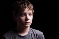 Sad teenage boy. Portrait sad teenage boy on a black background stock photography