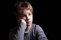 Sad teenage boy. Portrait sad teenage boy on a black background stock image