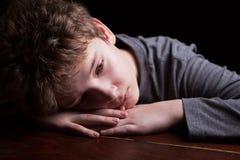 Sad teenage boy. Portrait sad teenage boy on a black background stock photos