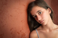 Portrait of a sad teenage girl. Leaning on a cracked wall with space for text royalty free stock photos