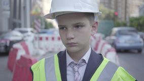 Portrait of sad tired little boy in constructor helmet on his head, and uniform looking away. Architect concept stock video