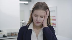 Portrait of sad tired young lady in formal clothes looking in camera. Woman with long hair had headache, she rubbing her stock video