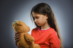 Portrait of sad or unhappy girl playing with teddy bear isolated on gray Royalty Free Stock Photography