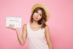 Portrait of a sad unhappy girl in summer hat. Holding her periods calendar and looking at camera isolated over pink background Stock Photo