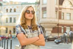 Portrait of sad unhappy teen girl with folded hands on city street, copy space stock photography