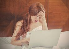 Portrait sad unhappy woman with laptop laying in bed of bedroom Stock Photography