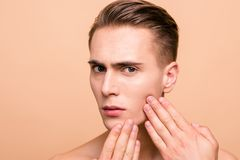 Portrait of sad, upset, frustrated, disappointed, naked brown ha. Ired man looking for acne on his face on pastel beige background touching cheek with fingers royalty free stock image