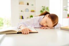Portrait of sad upset kid little person lie desk close eyes touch printed book sit interior class white blouse shirt stock image