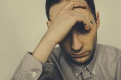 Portrait of sad upset young guy. The brooding man sitting and holding a hand over his head. In a bad mood. depression. headache, head pain. Young man squeezes stock photo