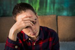 Portrait of sad upset young guy. The brooding man sitting and holding a hand over his head. In a bad mood. depression. headache, h. Ead pain stock photography