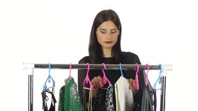Portrait of sad woman choosing dresses at a boutique. White stock video footage