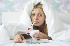 Portrait of sad woman with coffee mug taking temperature while wrapped in quilt on bed Stock Photo