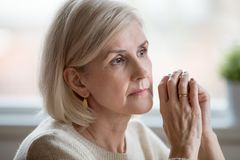 Portrait of sad woman cogitating sitting at home alone. Close up portrait of beautiful sad woman folding hands together near her face, thinking about life. Aging royalty free stock photography