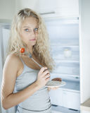 Portrait of sad woman having cherry tomato in kitchen Stock Photo