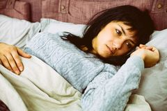 Portrait of sad woman lying in bed after breaking up with boyfriend Royalty Free Stock Photos